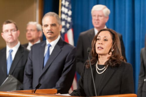 Kamala Harris with dark brown wavy hair wearing a black sweater and pearl necklaces standing to the right of four male representatives.