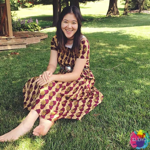 A young lady with dark hair wearing a multicolored shirt sitting down on the grass while staying positive.