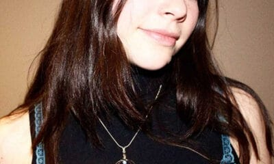 A young dark haired lady wearing a black shirt over a blue tank top stands in front of the camera.