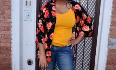 Woman in gold top with black and rose floral cardigan stands in front of a secured door outside of a brick building talking about a mental condition.