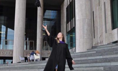 Young girl suffering from panic attacks stands on grey stairs in front of a tall grey building wears a black graduation gown happily tosses her graduation cap in the air