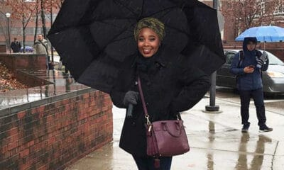 A young black lady carries an umbrella and her purse outside, while having a positive mindset.