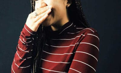 A young lady with long black braids is wearing a red and grey striped shirt laughing while covering her mouth with her right hand.