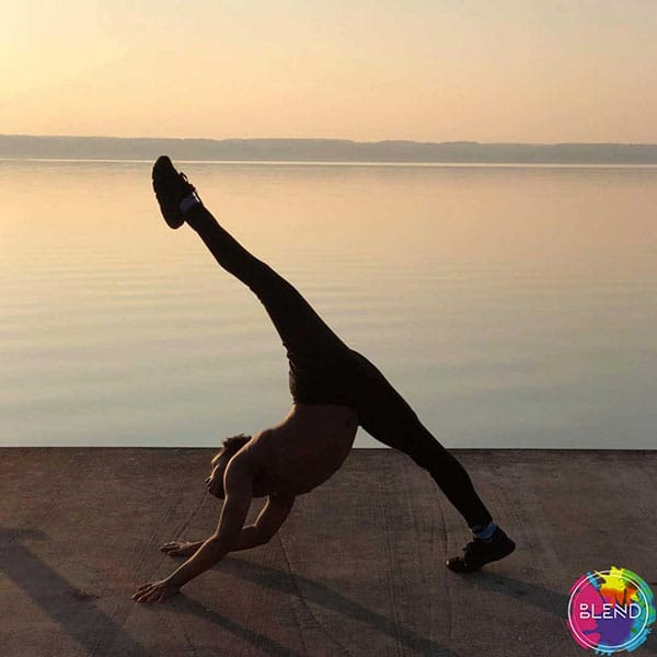 A young black man does a handstand in front of the sunset at the beach to improve his anxiety and stress