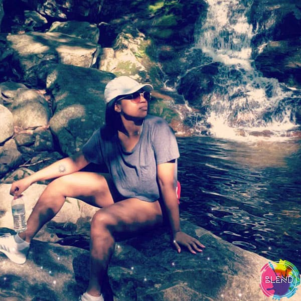 A young black lady with a hat and sunglasses wearing a grey shirt and shorts sits on a big rock at the lake.