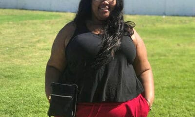 A young black plus-size girl with glasses wearing a black shirt and red jeans stands in the grass.