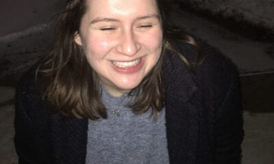 A young lady who is diagnosed with two disorders, does a complete smile at the camera. She has long brown hair, and she is wearing a black jacket and a grey shirt.