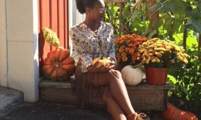 A black woman with glasses and a bun hairstyle sits down on a small bench near colorful plants, while she finds her inner happiness.