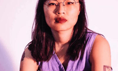 A young dark haired Asian American lady with glasses stands in front of the camera.