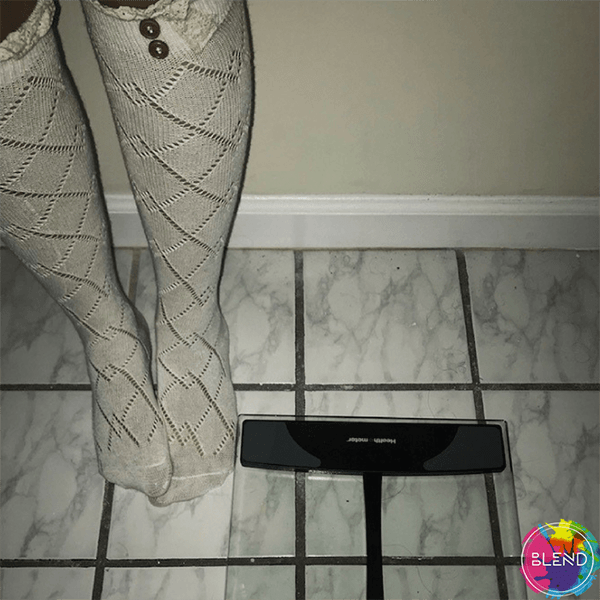 A young lady struggling with anorexia nervosa stands next to digital glass scale wearing white socks