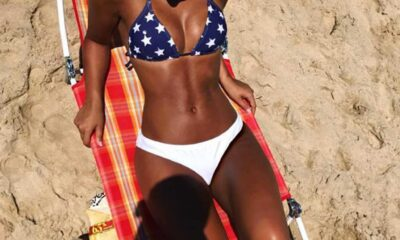 Tan lady who had negative body image lays on red gingham beach chair navy and white star bikini top and white bikini bottoms looking down at the sand.