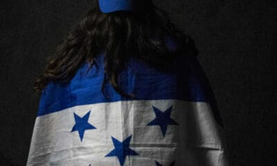 A young lady with wavy black hair wearing a blue and white shirt with blue stars on it has her back turned to the camera.