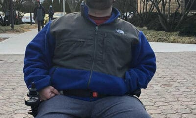 A tall and overweight man with cerebral palsy is wearing a heavy dark blue jacket, while sitting and facing the camera.