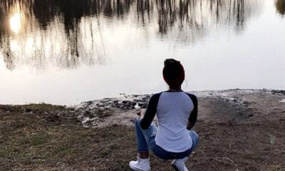 A young lady with a white and blue long sleeved shirt and white tennis shoes squats down on the dirt in front of a lake.