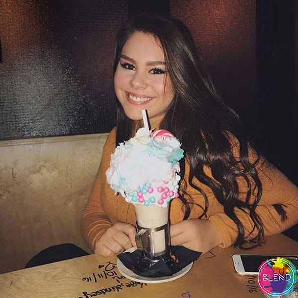 A young lady with dark hair orders a rainbow milkshake at a restaurant.