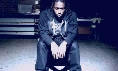 A young black man with dark braided hair sitting in a chair in a dark room near a table.