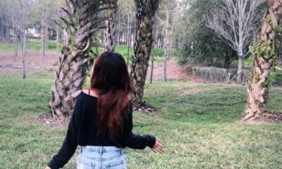 A young lady with dark long hair wearing a black shirt and shorts walks towards some pine trees in the woods.