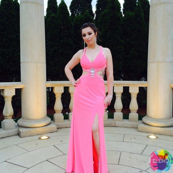 A tall young lady with dark hair wearing a pink dress stands outside of a pillared area.