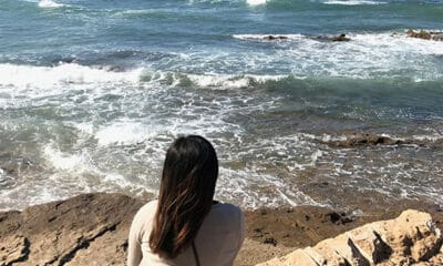 A young dark-haired lady sits on a rocky surface at the beach while watching the waves.