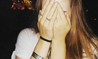 Young lady with brown hair wears a black hairband and multi colored bracelet on her wrist and two rings on her right hand, covers her face with hands.