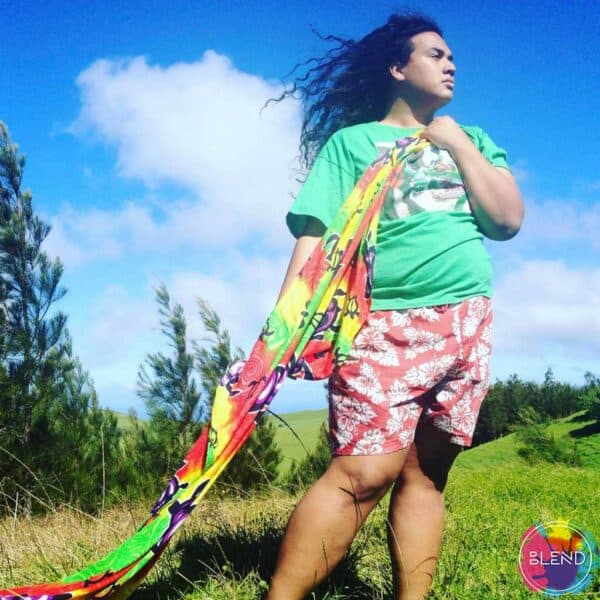 Young samoan man in red hawaiian shorts and green shirt, holds the uncomfortable edge of a colorful blanket blows in wind with his long black hair.
