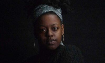 Young black woman with her hair in an updo, a scarf covers up part of her head, wears dangling earrings, looks seriously in the camera in a black room.
