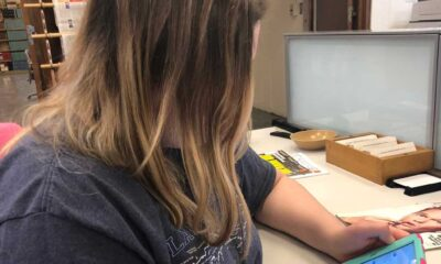 Girl with brown hair and dark grey shirt sitting at a table using her iPad.