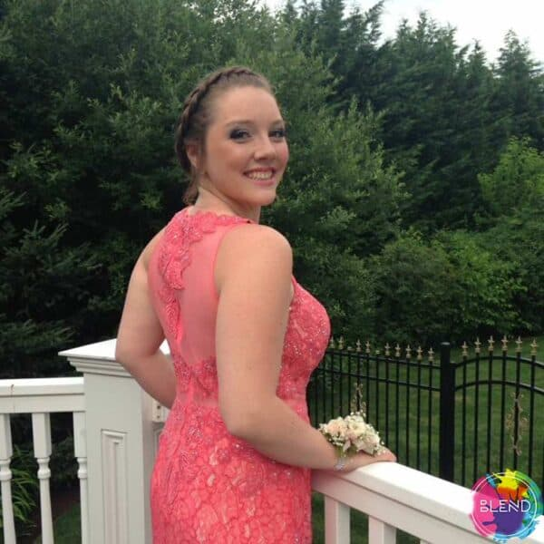A girl wearing a pink dress looks back at the camera smiling while standing on a white balcony