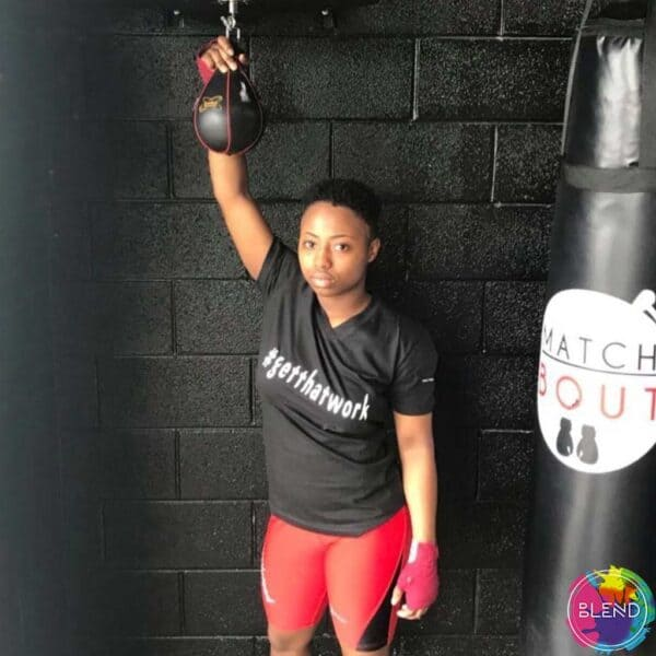 A black girl with dark hair wearing a black shirt, red shorts, and pink gloves standing in front a black wall.