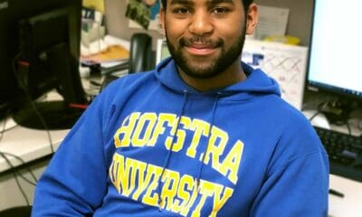 A male with black hair and a beard, wearing a blue Hofstra University sweatshirt sitting by two computers.