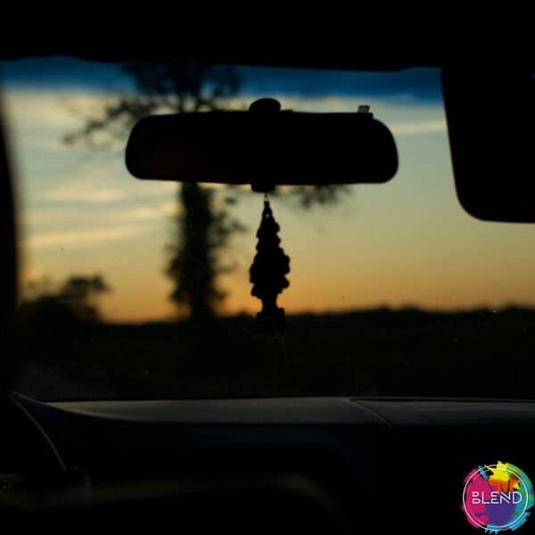 A sunset through a windshield with a little tree hanging from the rear view mirror.