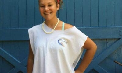 A girl standing and smiling in front of a blue wall wearing a white shirt and red headband.