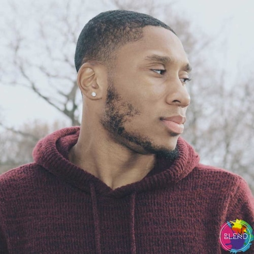 A black man with buzzed hair and a beard wearing a dark red sweater while standing outside looking briefly away from the camera.
