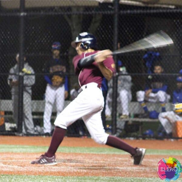 Author, in his white and maroon baseball uniform, swinging at the ball on homeplate.