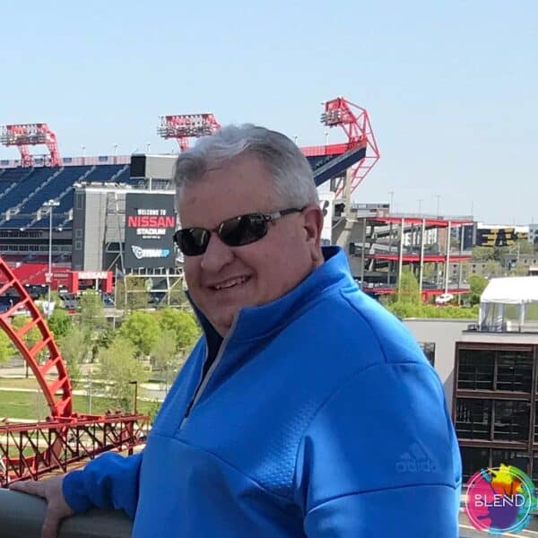 A man with grey hair wearing a blue sweatshirt and sunglasses, smiling, in front of Nissan Stadium.