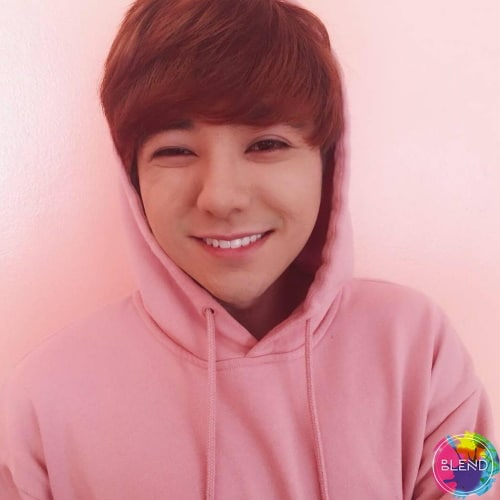 A person with short dark red hair wearing a pink hoodie while smiling at the camera.