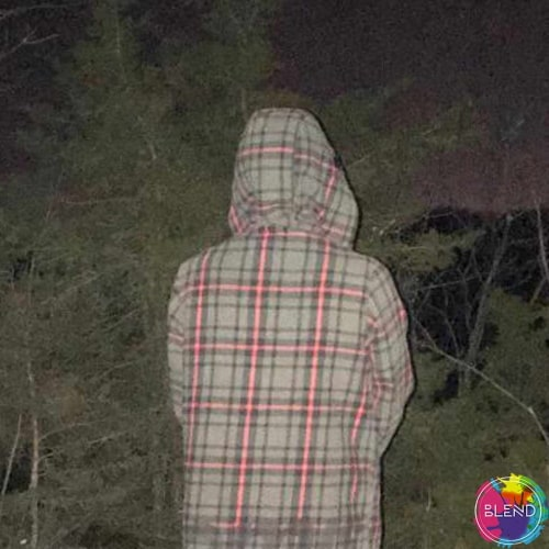 A person with their back turned while wearing a grey hoodie with pink checkered stripes, in the dark.