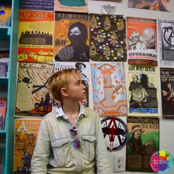 Young boy standing in front of a series of posters against the wall, looking up and over his left shoulder