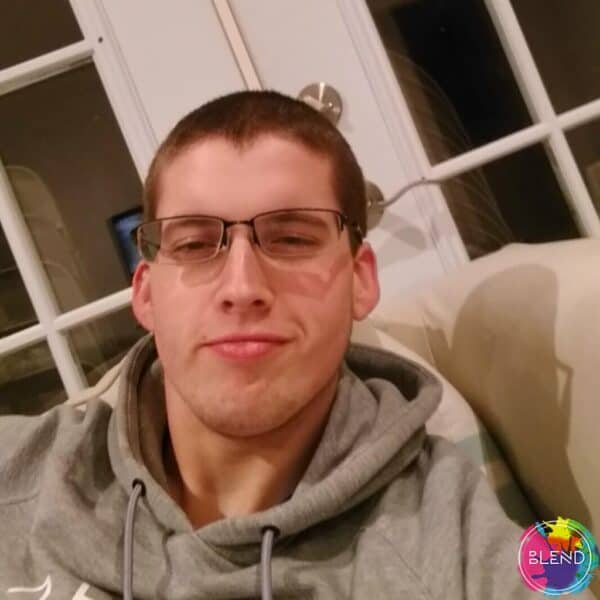 A man with buzzed brown hair, glasses and gray sweatshirt, sitting on a couch smiling at the camera.