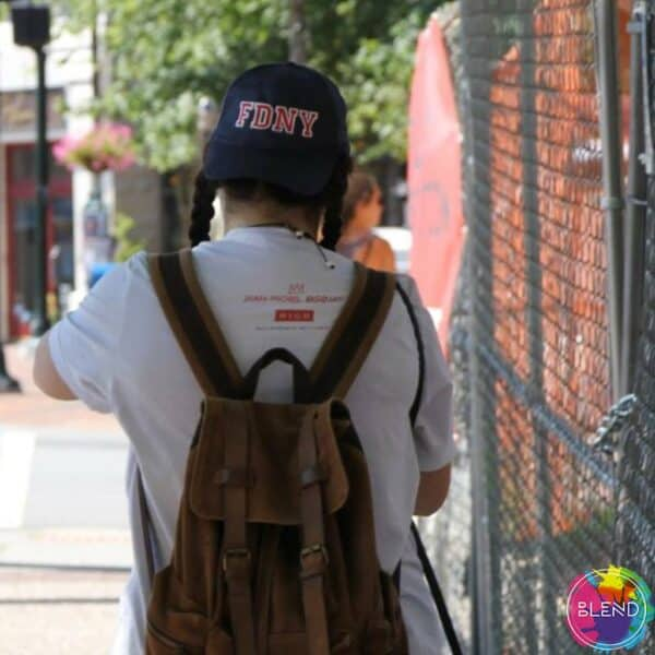 Author, in pig tails, an FDNY baseball cap, white shirt, and a backpack, walking away down the street.