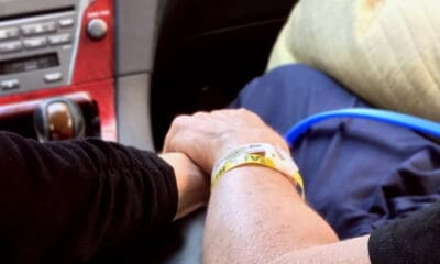 Two people holding hands in the car with one person wearing a black sweater, and one person in dark blue with a yellow wristband on their hand.