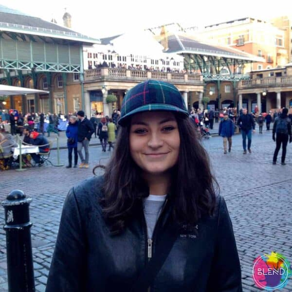 Author, with brown hair, a cap on, and a dark coat standing in a courtyard with people walking and businesses behind her