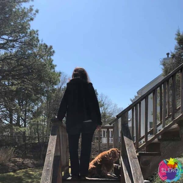 A woman with dark hair, wearing a black jacket standing on a wooden staircase in her backyard with her dog.