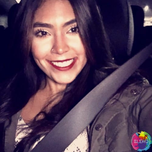 A young lady with dark long hair and red lipstick wearing a dark grey vest and a white shirt wearing a seatbelt in a vehicle.