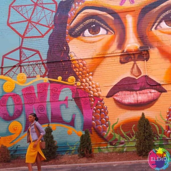 A girl with long dark hair, wearing a yellow dress and jean jacket standing next to a wall with a mural of a women on it.