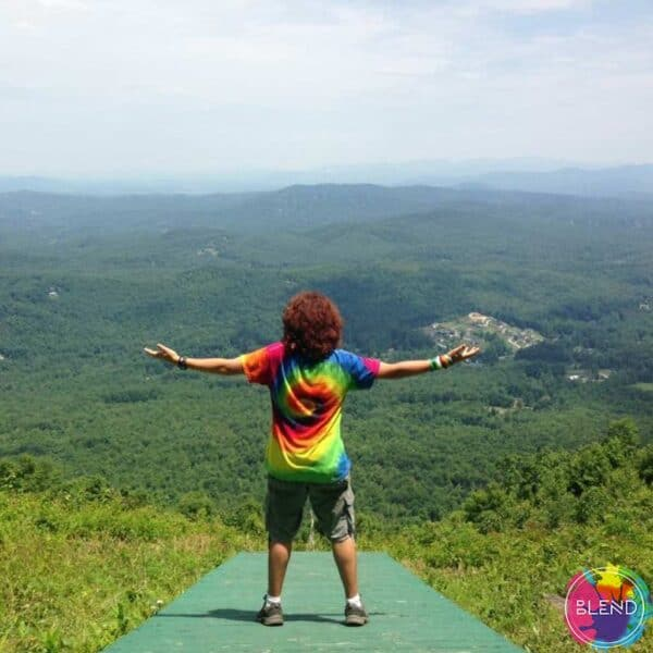 The author wearing a tye dye shirt and cargo shorts while looking at a view from a mountain top.