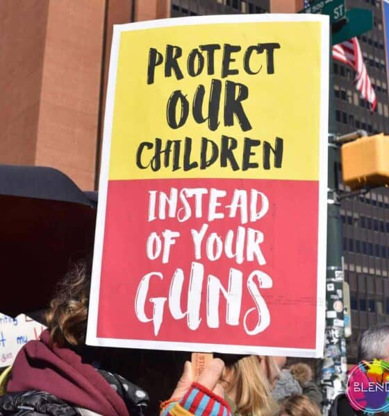 "A person holding a sign saying, ""Protect our children, instead of your guns"" at a protest"