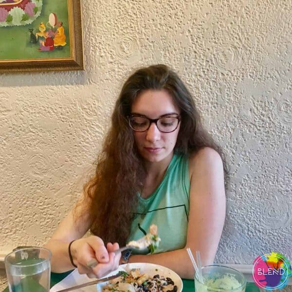 A girl with long brown hair and glasses wearing a cyan shirt while eating food.