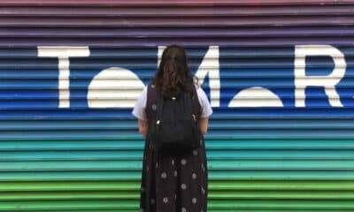 """A young woman with black wavy dark hair with her back turned to a rainbow wall with part of """"Tomorrow"""" written in white."""