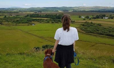 A brunette woman, in a white shirt, black pants, black sweater tied around her waist, standing next to her brown dog overlooking a vast greenscape